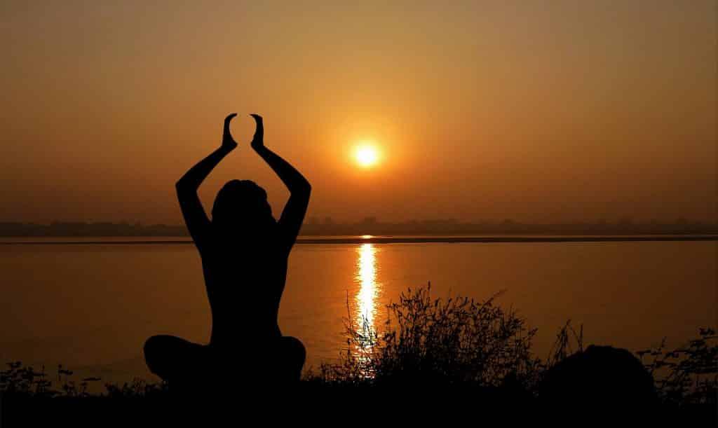 Imagem da silheuta de uma mulher em posição de meditação. Ela está com as duas mãos levantadas contemplando o lindo por do sol.