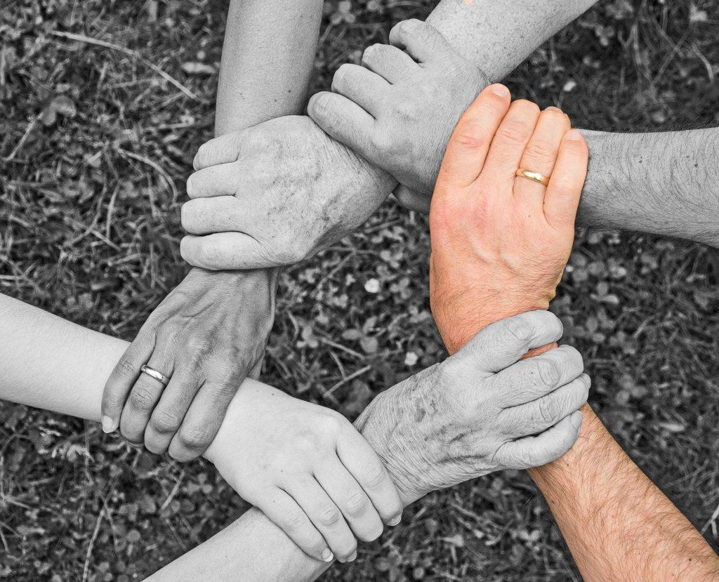 Imagem de várias mãos de pessoas jovens e de pessoas idosas formando um quadrado  representando o espírito de equipe.