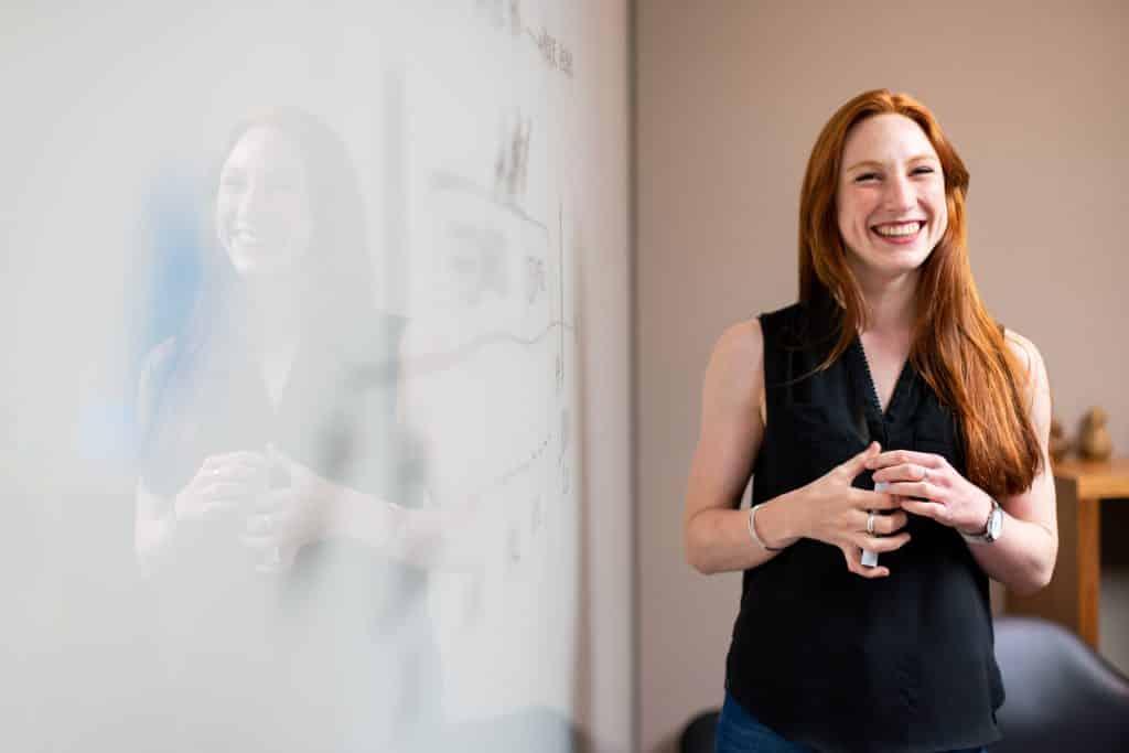 Professora em pé, sorrindo, ao lado de um quadro branco.