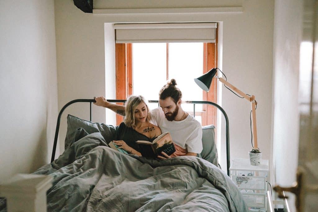 Homem e mulher sentados na cama lendo um livro.