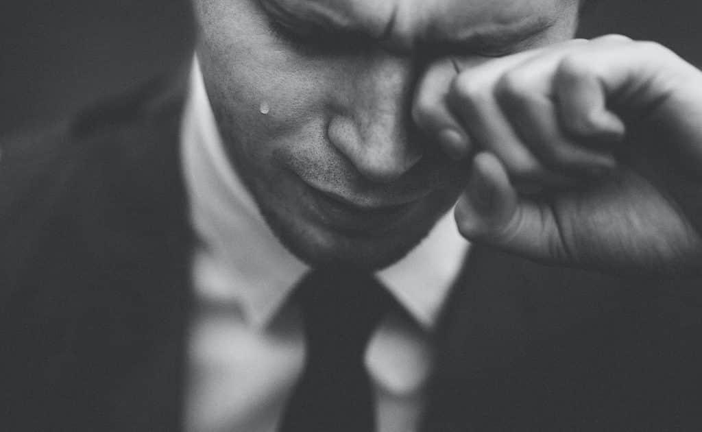 Homem chorando e limpando suas lágrimas com sua mão