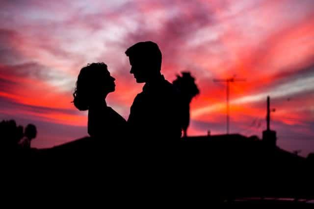 Silhueta de casal com céu rosa ao fundo
