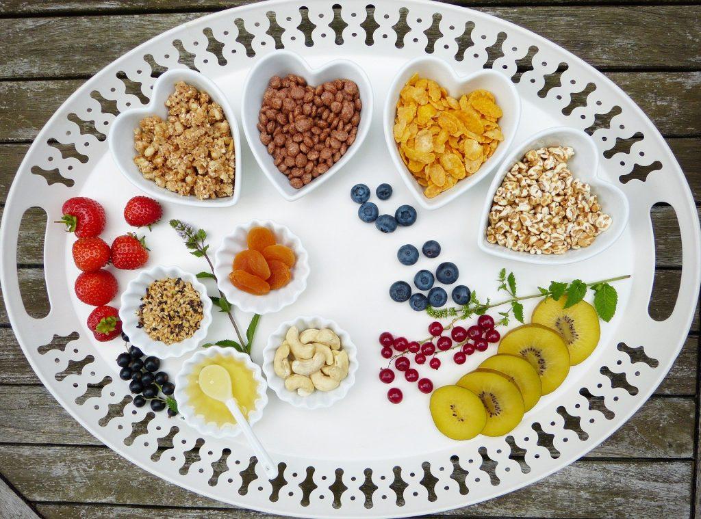 Imagem de um prato grande branco dividido em várias porções com alimentos variados como: frutas, grãos, sementes, óleos.