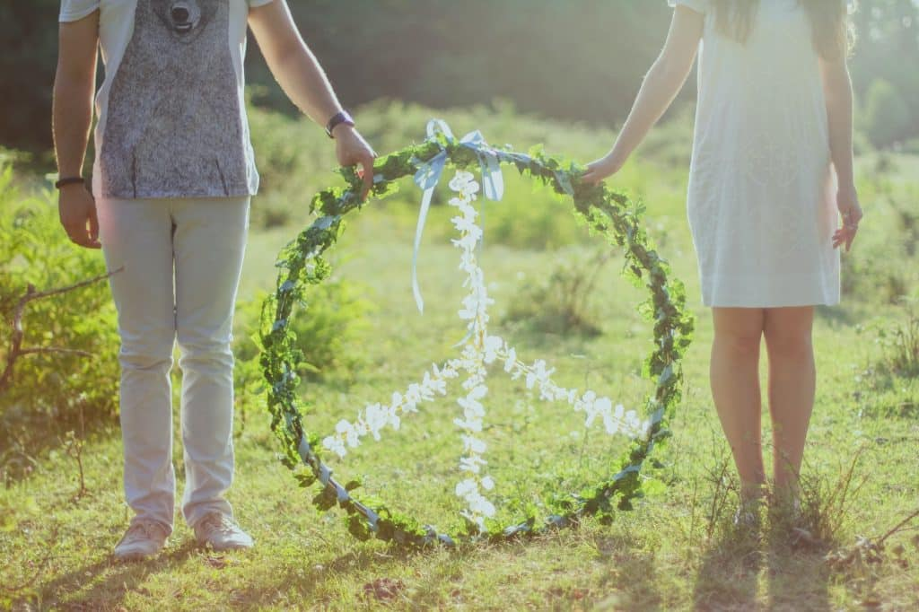 Duas pessoas segurando arco com o símbolo da paz, feito com folhas verdes e flores brancas.