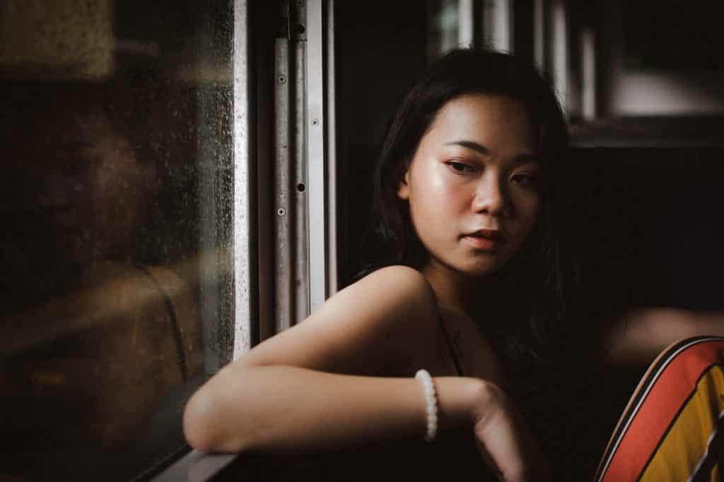 Mulher encostada em uma janela pensativa