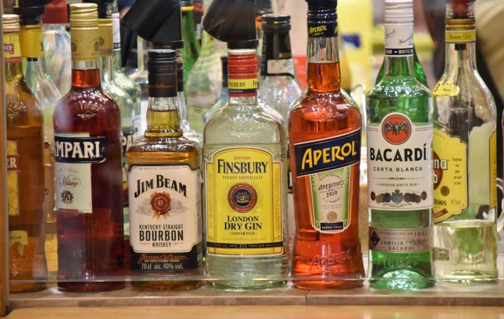 Garrafas de bebidas alcoólicas enfileiradas em um bar.