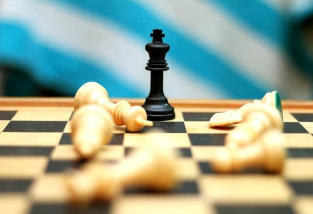 Tabuleiro de xadrez com peças brancas derrubadas e apenas uma peça preta em pé