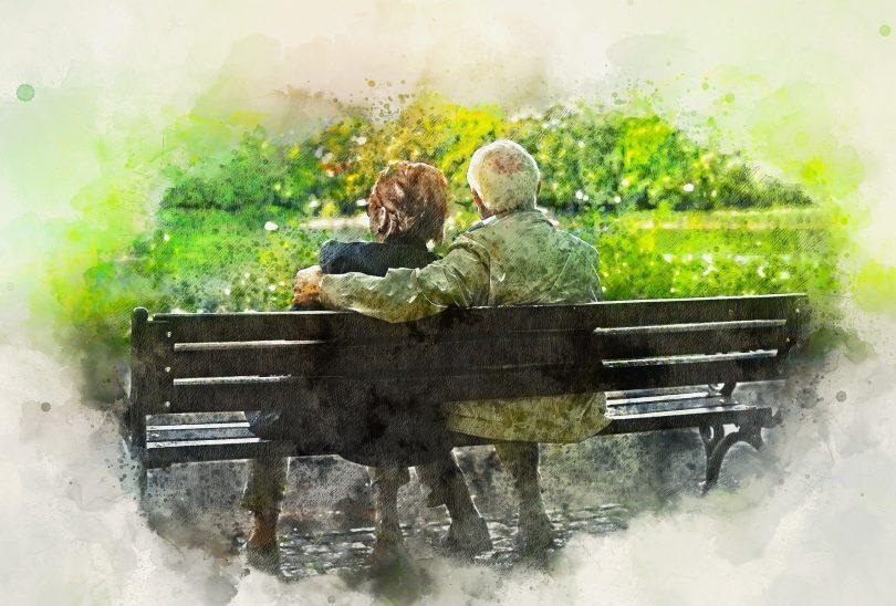 Imagem de um casal de idosos (avós) sentacdos em um banco de mandeira olhando para um lindo jardim.