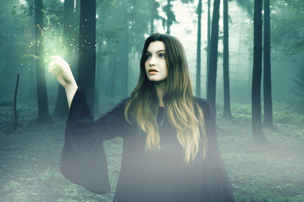 Imagem de uma linda mulher bruxa de cabelos longos e vestido preto no meio de uma floresta.