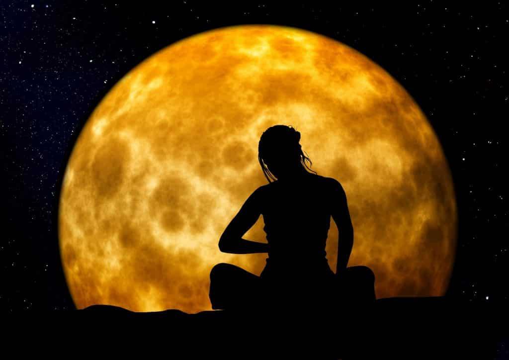 Imagem da silhueta de uma mulher sentada e ao fundo uma linda Lua Cheia,