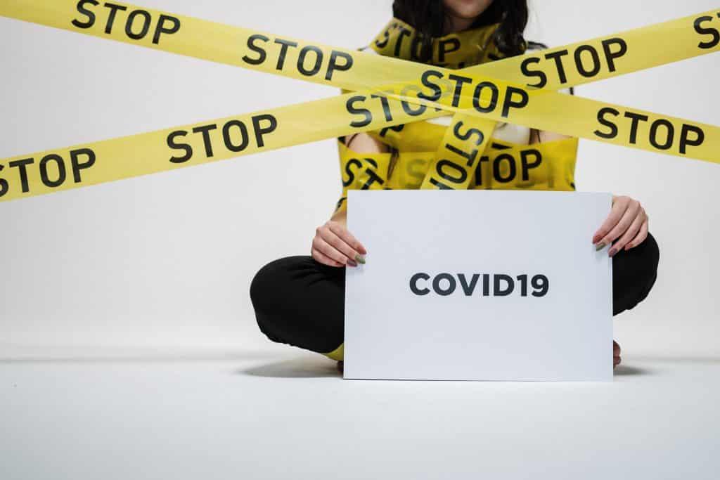 """Mulher imobilizada por faixas segurando uma placa com os escritos """"COVID-19""""."""