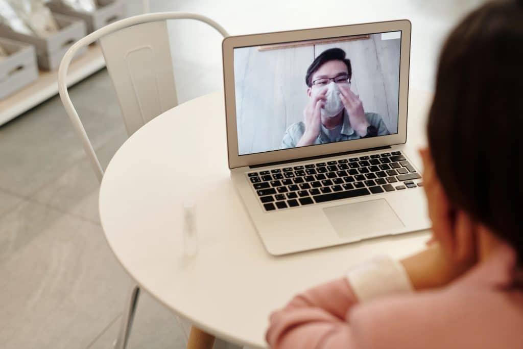 Pessoa fazendo videochamada com um homem de máscara, durante a quarentena.