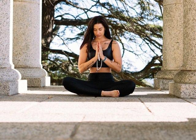 Mulher sentada em posição de lótus meditando