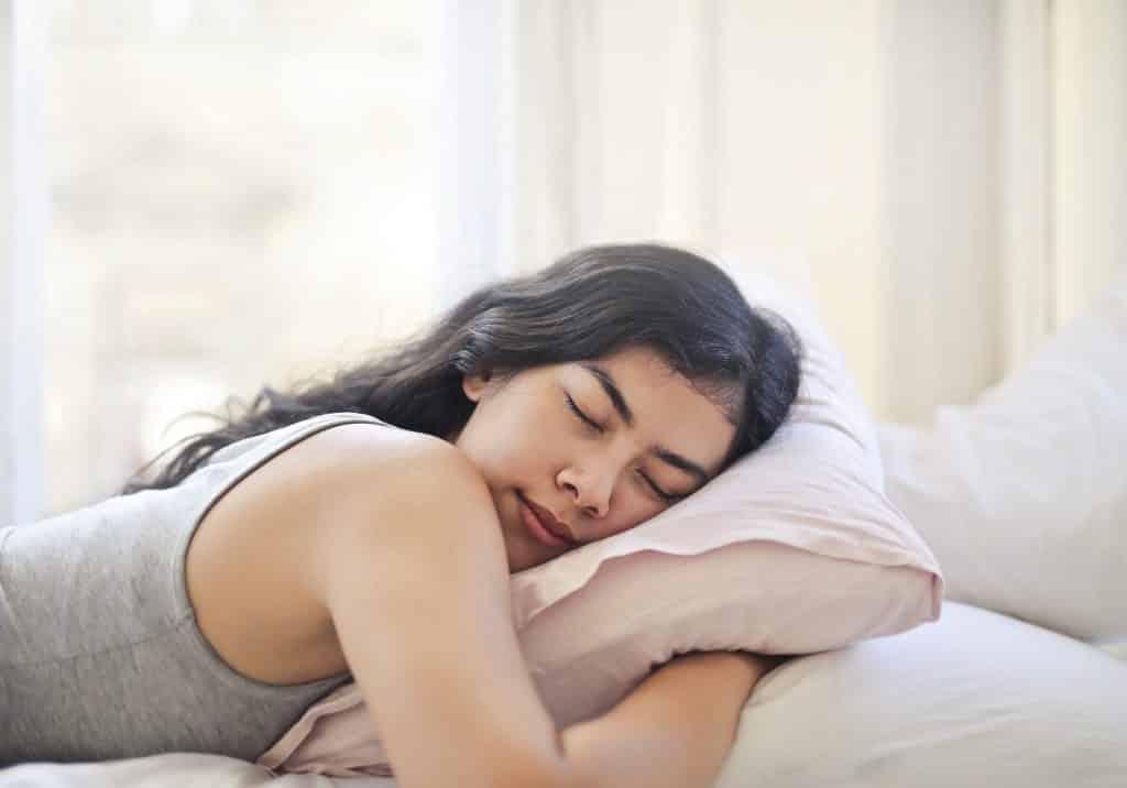 Mulher deitada na cama, de bruços, dormindo enquanto abraça o travesseiro.
