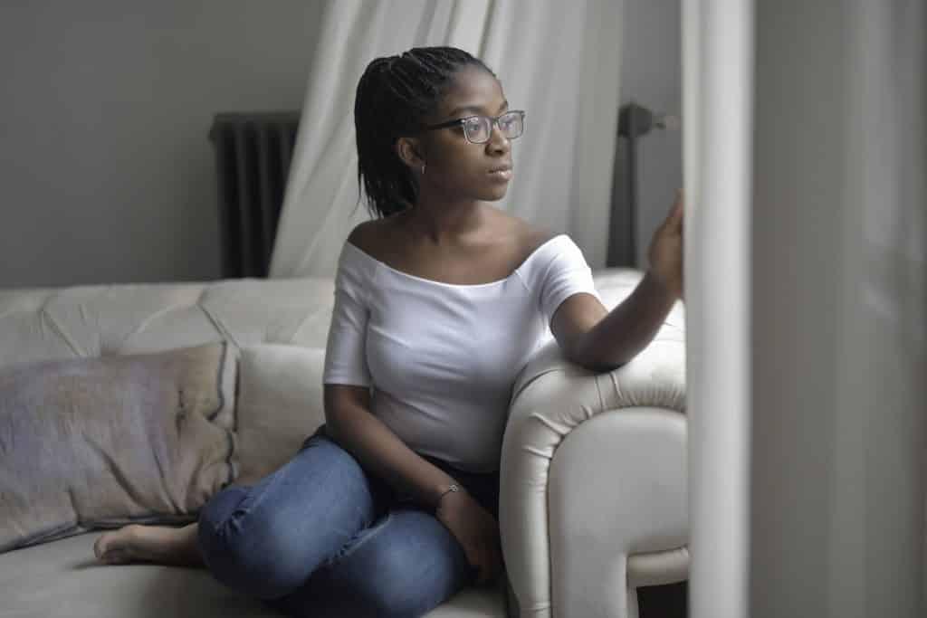 Mulher sentada no sofá de casa, olhando pela janela com expressão pensativa.
