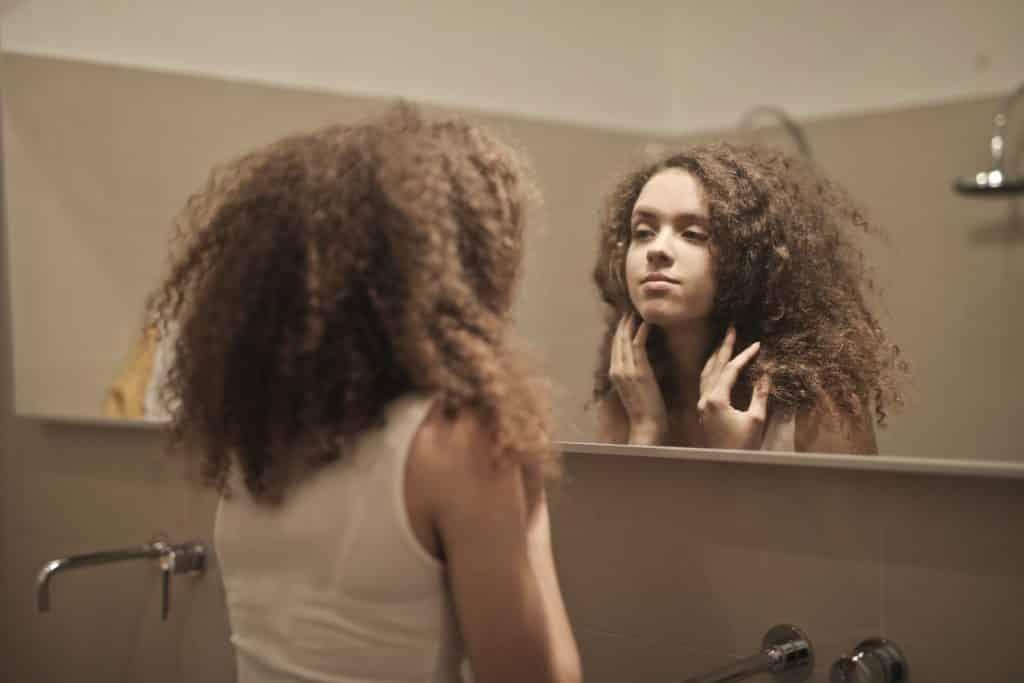 Mulher de cabelos cacheados olhando a si mesma no espelho de um banheiro.