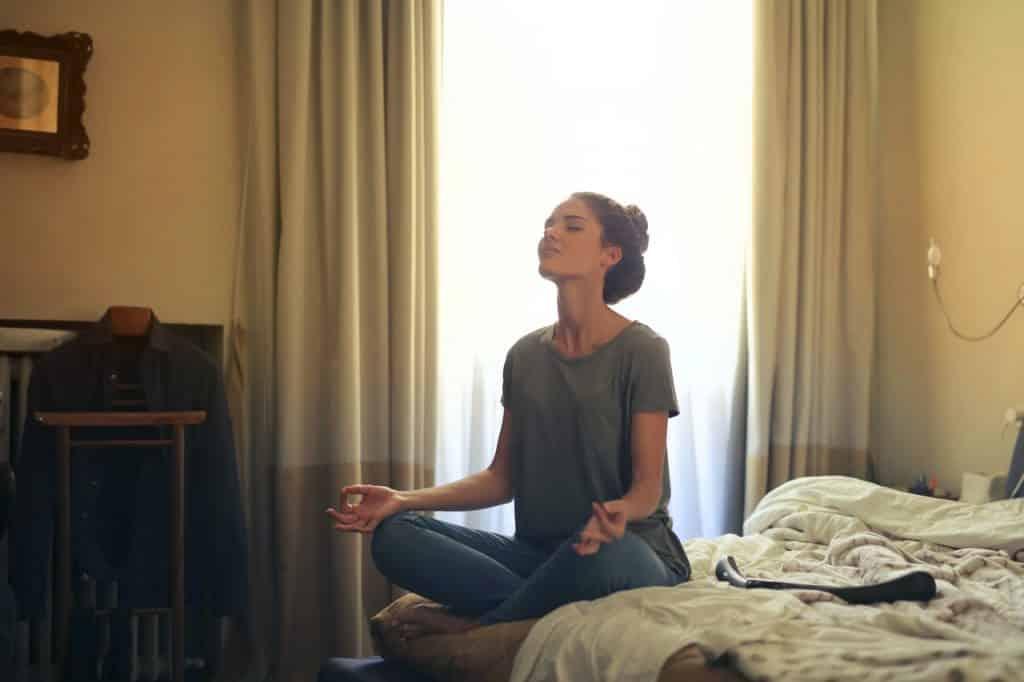 Mulher sentada com as pernas cruzadas em cima de uma cama, apoiando as mãos em seus joelhos, meditando.