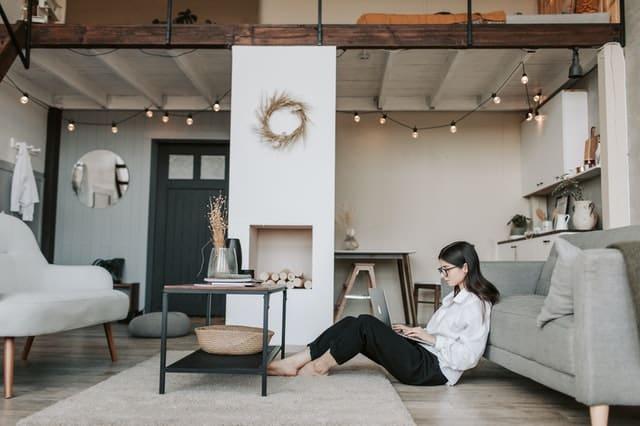 Mulher sentada no chão da sala de casa com notebook no colo