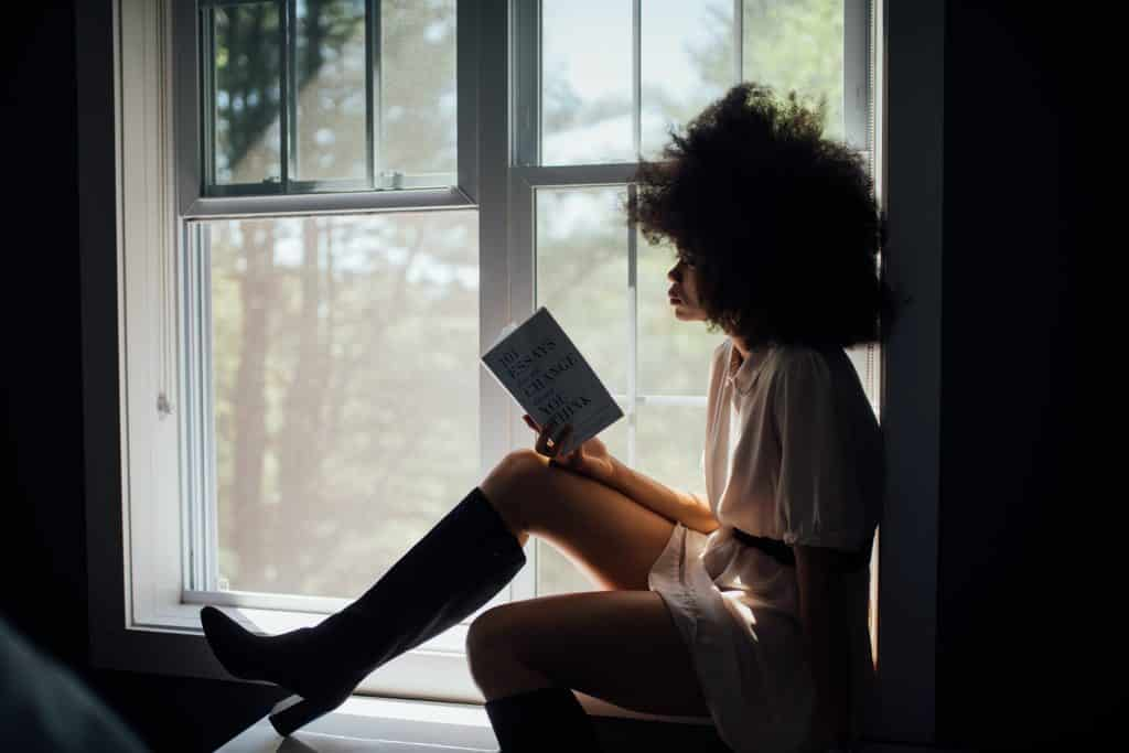 Mulher de botas e vestido sentada na janela, lendo um livro.