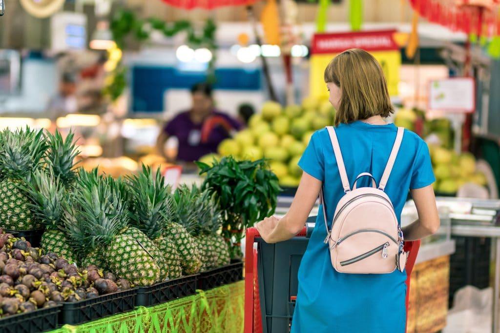 Mulher fazendo compras em um supermercado, na seção de frutas