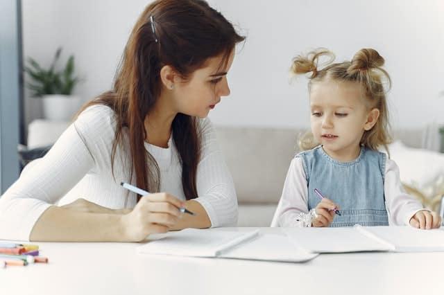 Mãe e filha desenhando em cadernos em mesa