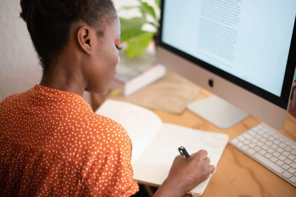 Mulher escrevendo em um caderno sobre uma mesa com um computador.