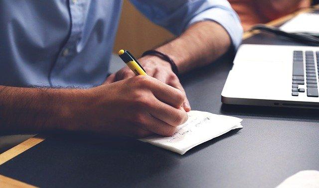 Pessoa em frente a notebook, escrevendo em um caderno ao lado dele.