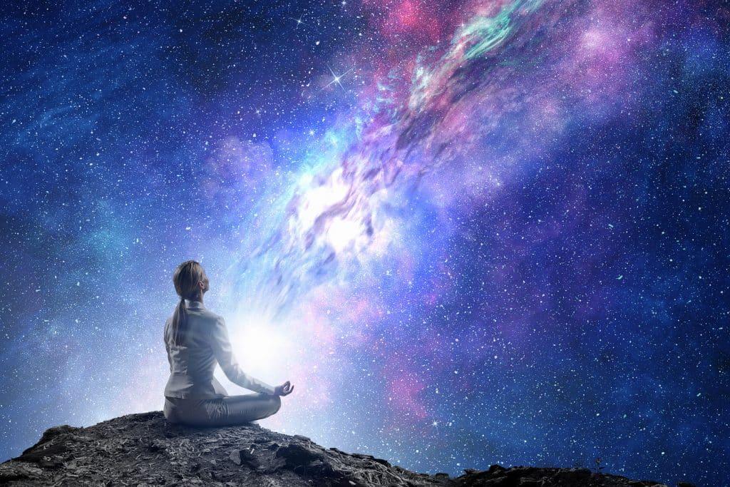 Mulher sentada de pedras cruzadas, meditando, em frente a um céu com luzes roxas e azuis, e um feixe branco que sai da mulher e vai até o ponto mais alto do céu na imagem.