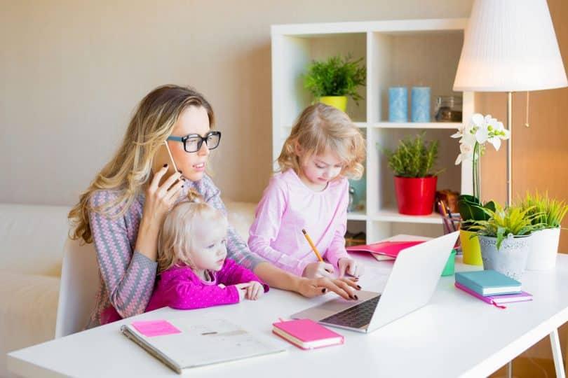 Mulher em frente de um computador, com uma menina pequena em seu colo, e outra de pé ao lado.