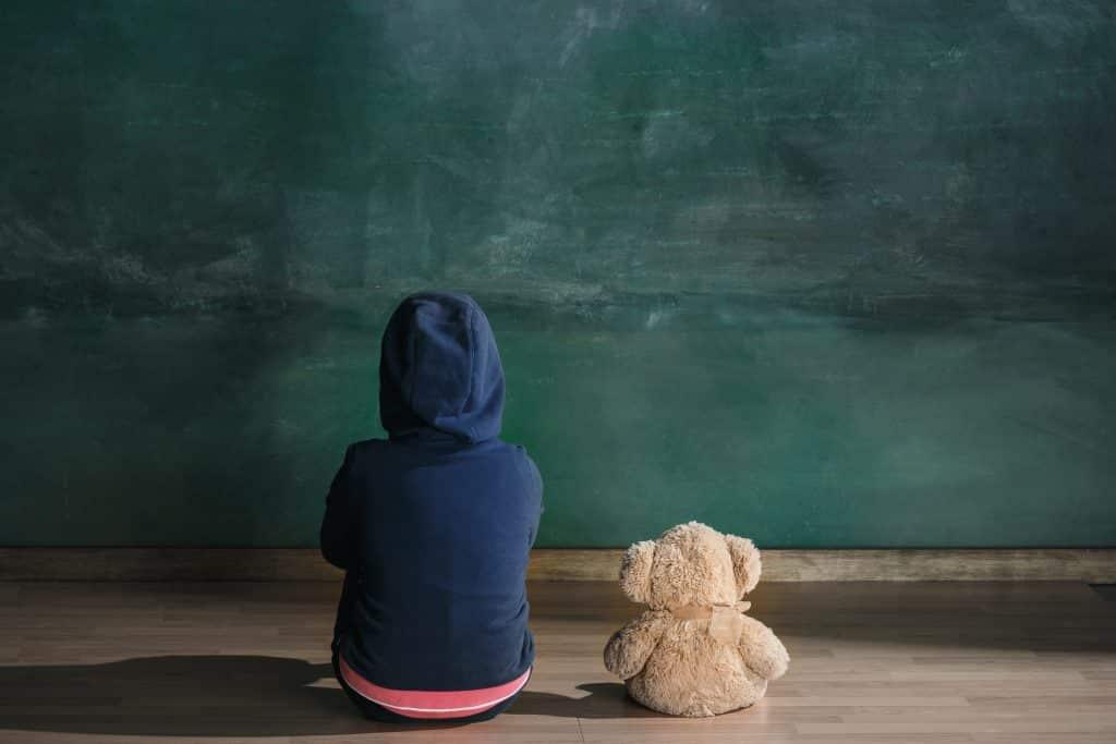 Imagem de um criança sentada no chão olhando para o quadro negro. Ela usa uma blusa azul marinho com capuz e ao lado dela está um ursinho de pelúcia.