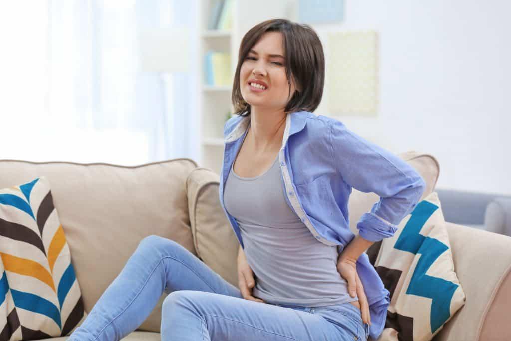 Mulher sentada em seu sofá sentindo dor