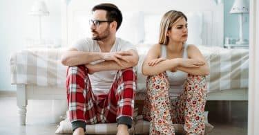 Homem e mulher usando pijamas, sentados lado a lado no chão, em frente a uma cama. Ambos olham para o lado oposto ao outro.
