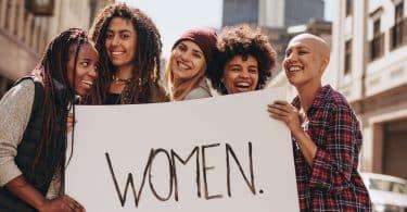 """Mulheres na rua segurando cartaz escrito em inglês """"women"""""""
