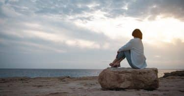 Mulher pensativa sentada em uma pedra da praia olhando para o mar