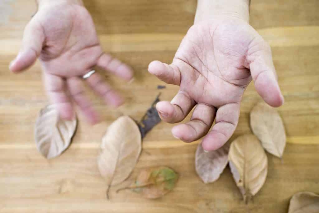 Imagem de mãos trêmulas de um senhor diagnosticado com parkinson.