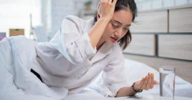 Mulher doente deitada na cama com a mão sobre a cabeça enquanto toma remédios.