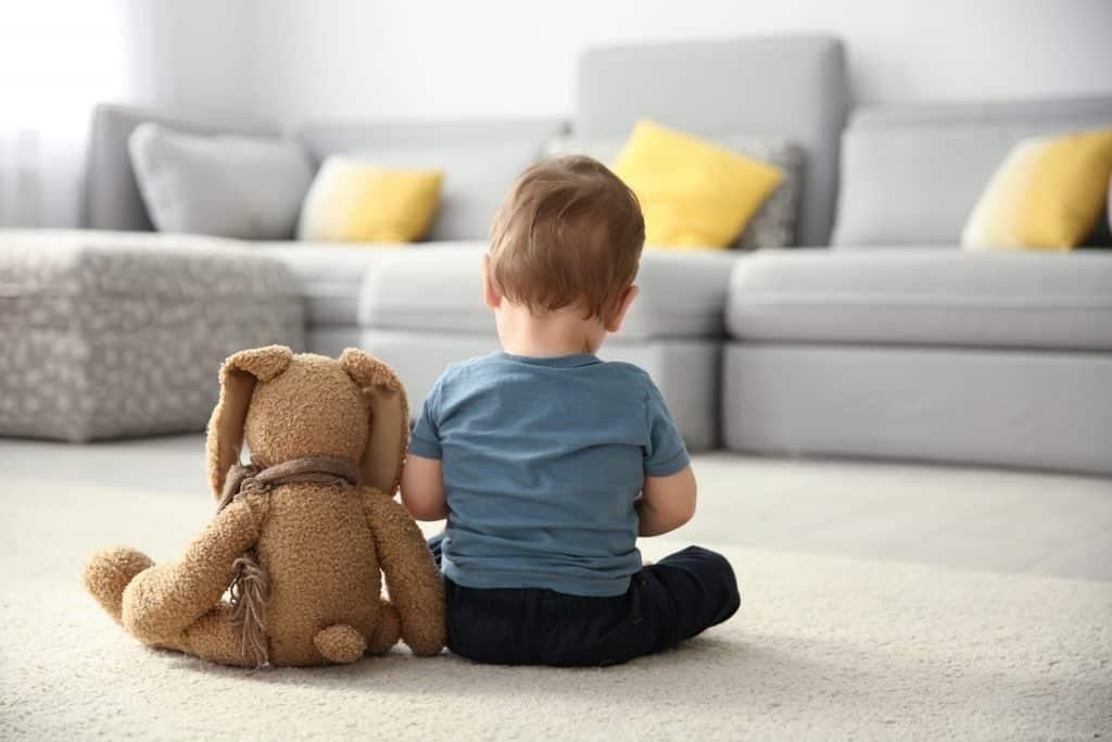 Imagem de um pequeno garoto autista. Ele está de costas, sentado no chão da sala ambientada com sofás cinzas e almofadas amarelas e cinzadas. Ao lado dele um cachorro de pelúcia.