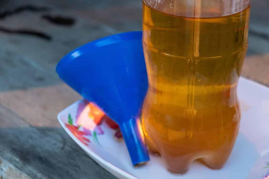 Imagem de uma garrafa transparente cheia de óleo de cozinha pronto para reuso.
