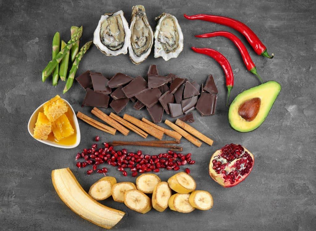 Alimentos afrodisíacos organizados em pequenas porções: aspargos, ostras, pimentas, canela, romã, abacate, banana e mel