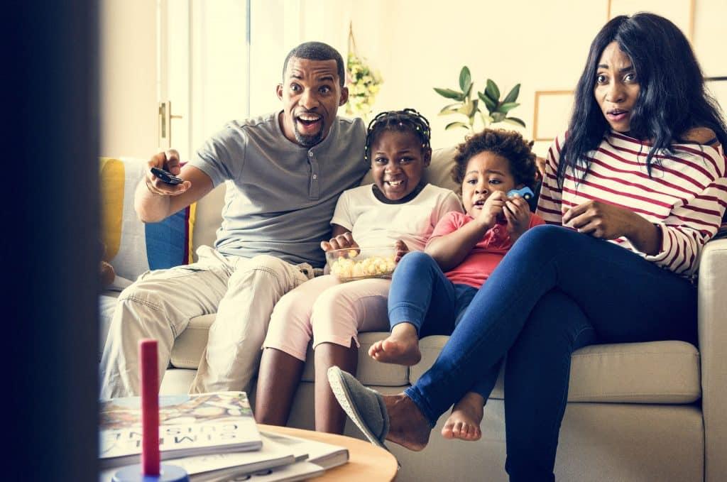 Família reunida no sofá da sala assistindo filme