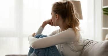 Garota sentada em sofá olhando para janela com mão apoiada no rosto