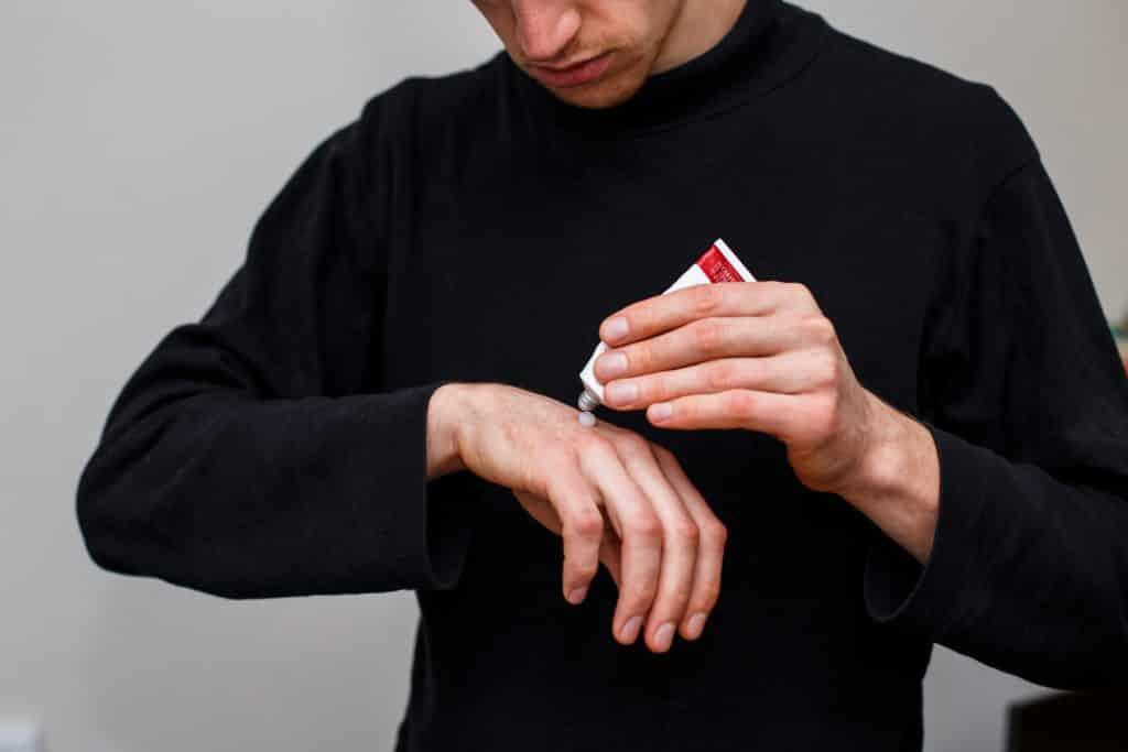 Imagem de um homem vestindo uma blusa de manga longa na cor preta. Ele está passando pomada em uma das mãos que está com aspecto da psoríase.
