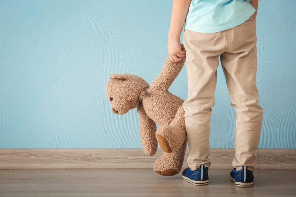 Imagem de uma criança autista de costas olhando para uma parede na cor azul. Em uma das mãos ela segura um ursinho de pelúcia marrom.