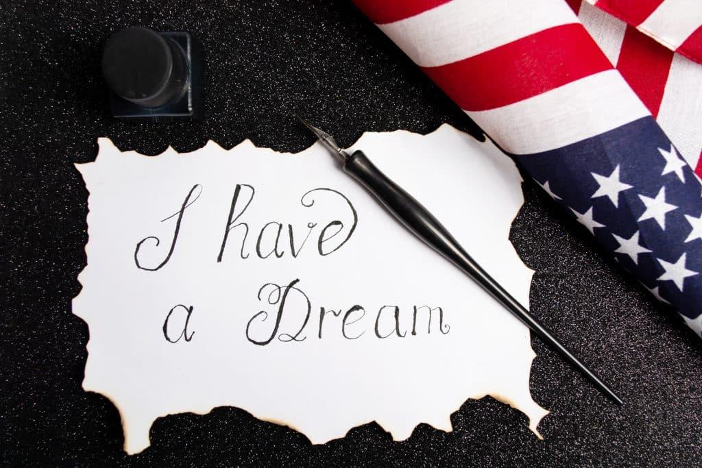 """Imagem de um cartaz branco com os dizeres: """"Eu tenho um sonho"""" ecrito em inglês - """"I Have a Dream"""" - do discurso de Martin Luther King - ao lado do cartaz um caneta tinteiro e a bandeira dos Estados Unidos."""