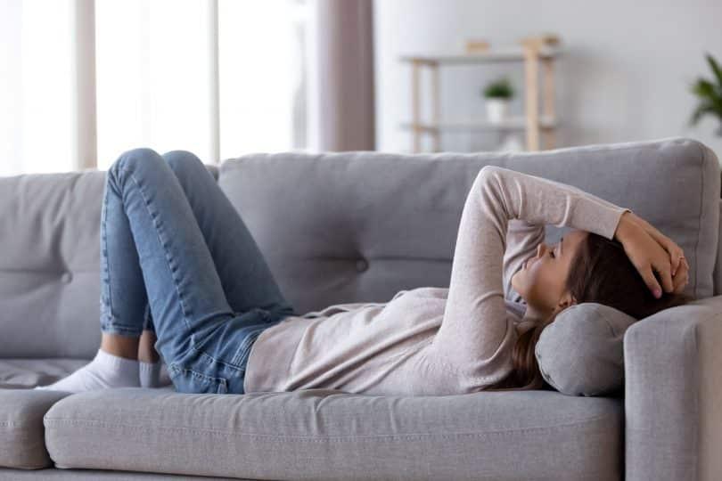 Mulher deitada em sofá com as pernas flexionadas e as mãos na cabeça. Ela parece irritada e exausta.