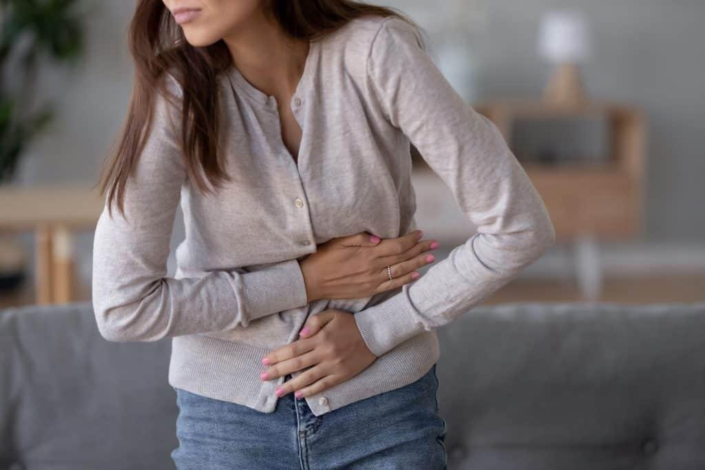 Mulher em pé em sua sala com dores na barriga