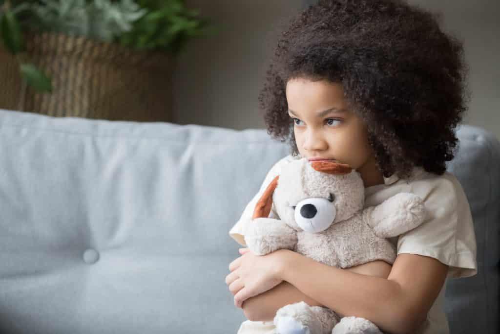 Imagem de uma criança afrodescendente sentada em um sofa de couro branco. Ela segura em seu colo um ursinho de pelúcia bege.