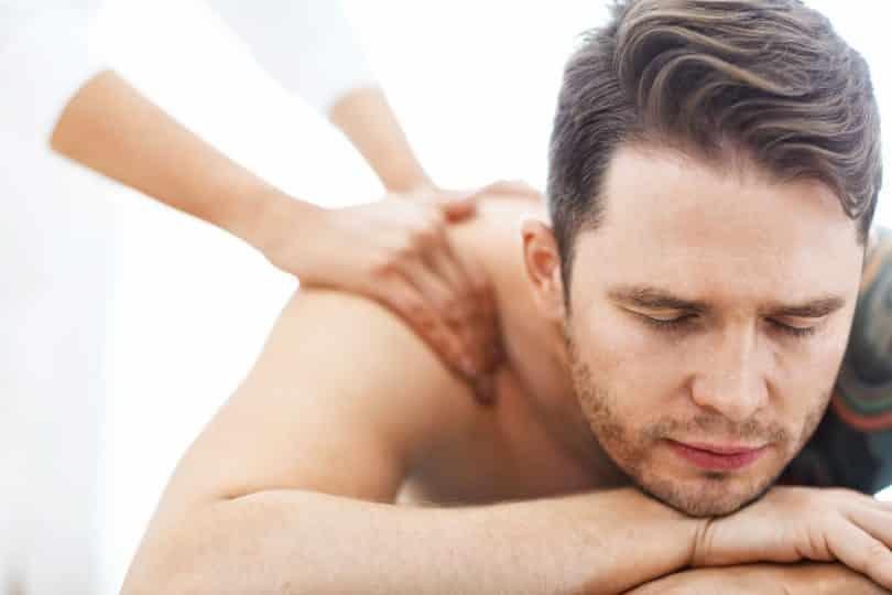 Homem de olhos fechados recebendo massagem nas costas.