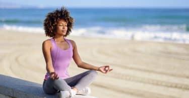 Mulher de cabelos cacheados sentada na beira da praia, meditando com os olhos fechados.