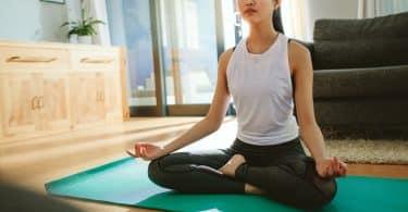 Mulher sentada, com as pernas cruzadas, meditando no chão de uma sala.